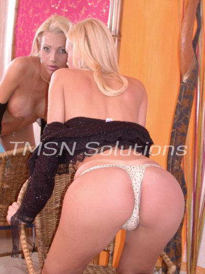 Transexual Blonde bent over looking at her package in the mirror.