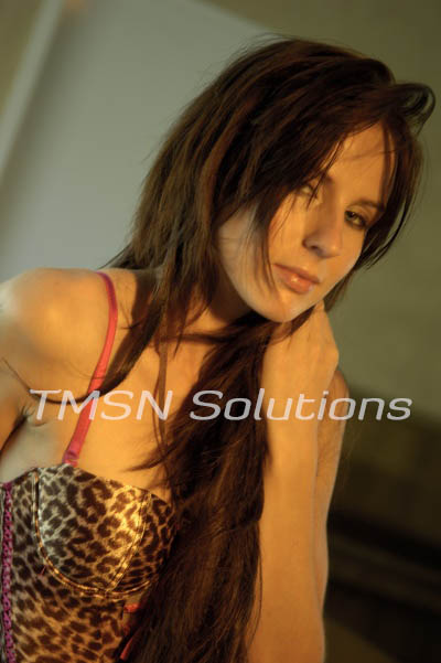 Brown haired girl playing with her hair looking at the camera in a leopard print corset top smiling