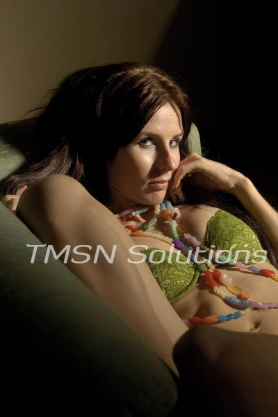 Brown haired girl on a couch knees to her chest in a lime green bra and panties biting her finger looking at the camera