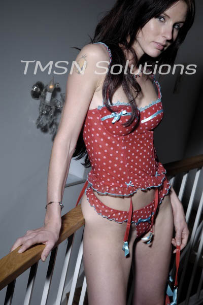 Brown hair in a red polka dot corset and matching panties smiling at the camera leaning on a staircase rail